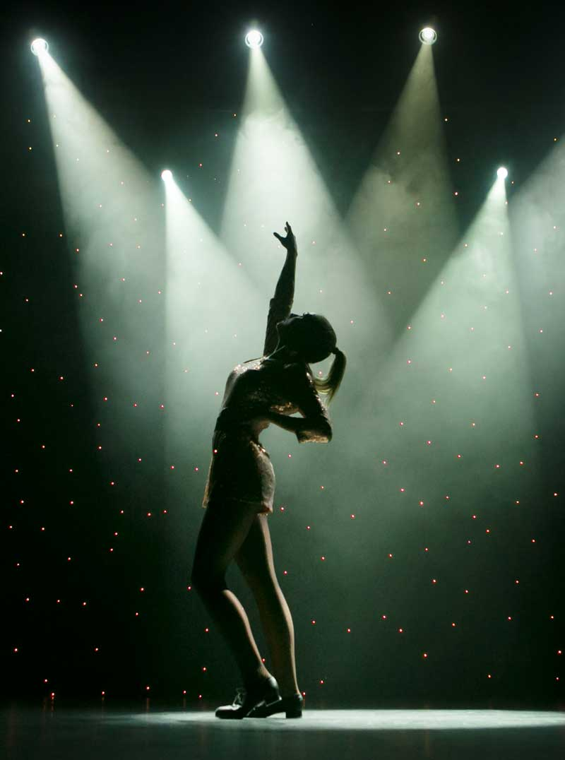 a dancer under the spotlights at the Aviv Annual Show